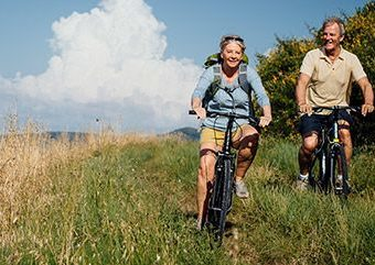 Couple bike riding through long grass